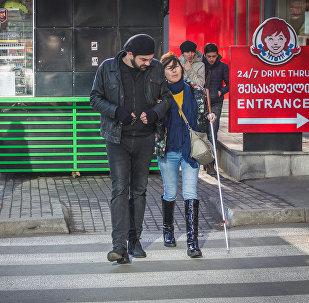 Гия Джваршеишвили помогает девушке с белой тростью перейти дорогу