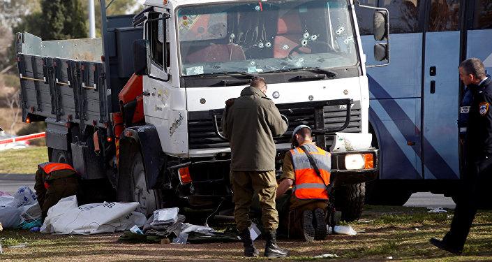 Израильские солдаты работают на месте, где грузовик въехал в группу израильских солдатов на популярной набережной в Иерусалиме
