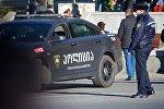 Сотрудник полиции у патрульной машины