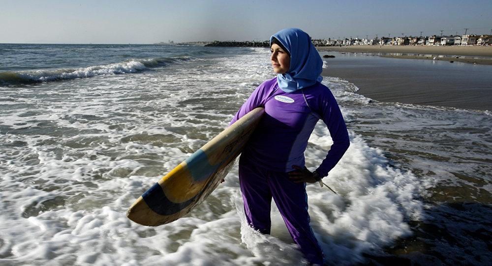 Сама Варех в буркини с доской для серфинга на пляже Ньюпорт, Калифорния
