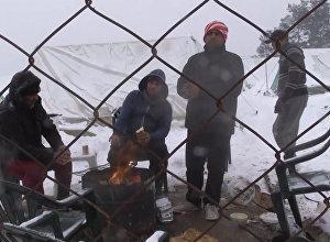 სალონიკში თოვლის მოსვლის შემდეგ მიგრანტების ბანაკში ლტოლვილებმა კოცონი დაანთეს