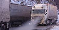 Очередь из грузовых фур зимой в горах