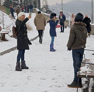 Туристы фотографируются на фоне Тбилиси на смотровой площадке на верхней станции канатки у крепости Нарикала