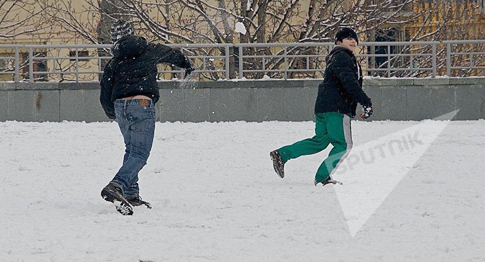 Дети играют в снежки на одной из тбилисских улиц