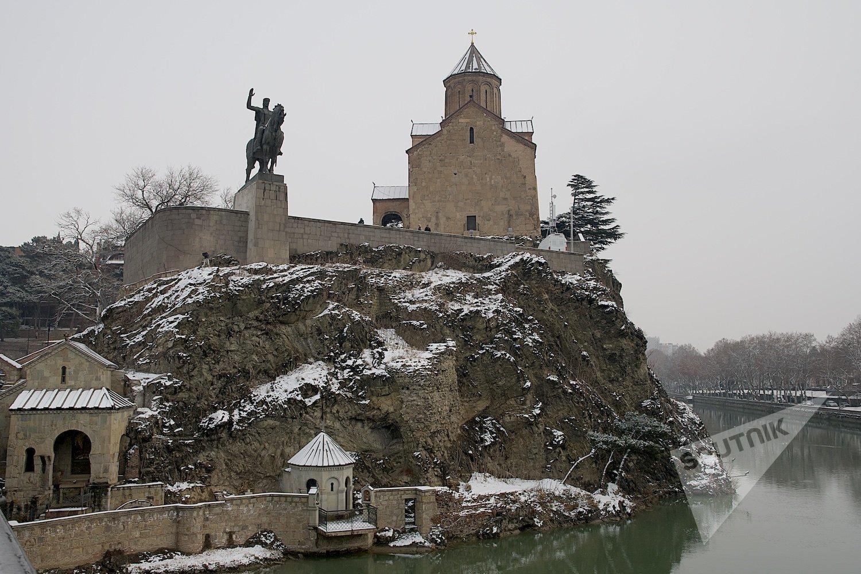 Вид на Мехетскую церковь и памятник царю Вахтангу Горгасали в центре Тбилиси зимой в снег