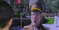 Мужчина смотрит на трансляцию выступления министра госбезопасности Северной Кореи Ким Вон Хона