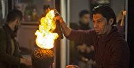 Палестинский парикмахер Рамадан Эдван делает прически с помощью огня