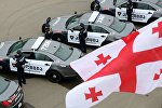 Патрульная полиция Грузии на фоне грузинского флага