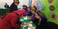 Женщина принимает участие в голосовании на выборах президента Туркменистана