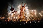 Люди смотрят на огненного дракона, сделанного из петард, китайских фонариков и фейерверков во время исполнения праздничного танца дракона участниками Фестиваля фонарей в провинции Гуандун в Китае.