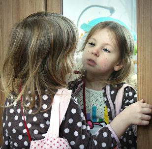 ბავშვი სარკეში საკუთარ გამოსახულებას აკვირდება
