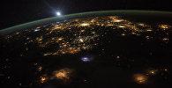 Ночная Земля: вид на восход солнца над поверхностью планеты из космоса с международной космической станции, на высоте более 350 км над поверхностью Земли