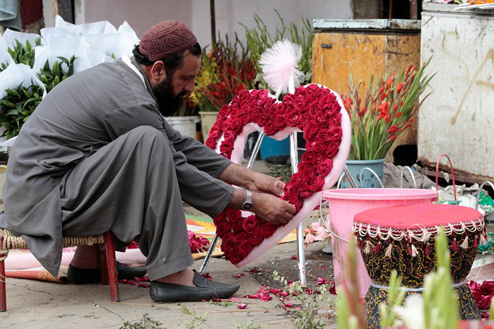 ისლამაბადეში ყვავილების ბაზრობაზე მამაკაცი გულის ფორმის თაიგულს კრავს, პაკისტანი