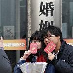 ახალდაქორწინებულები ოფიციალური ქორწინების მოწმობას უჩენებენ პეკინში, ჩინეთი
