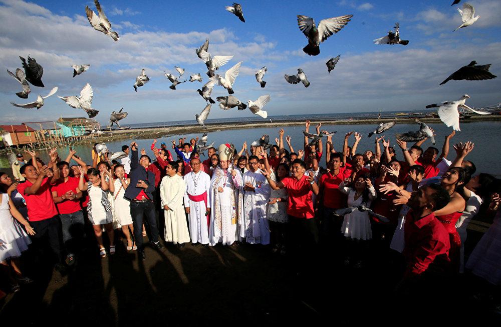 ახალდაქორწინებულები ჰაერში უშვებენ მტრედებს საყოველთაო ქორწინების ცერემონიის დასრულების შემდეგ ქალაქ კავიტეში, ფილიპინები