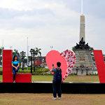 შეყვარებულები სამახსოვრო ფოტოს იღებენ უზარმაზარ წარწერასთან LOVE (სიყვარული) მანილში, ფილიპინები