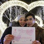 ახალდაქორწინებულები ქორწინების მოწმობას უჩვენებენ შეყვარებულთა ხეივანზე კაზანში