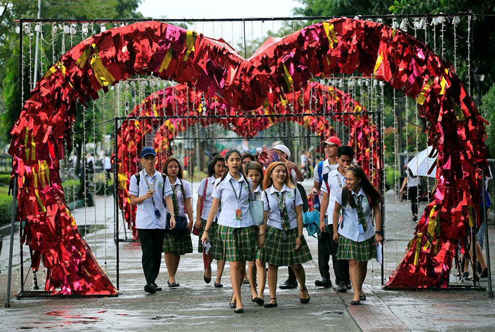 სტუდენტები მორთულ ლუნეტა-პარკში სეირნობენ მანილში, ფილიპინები
