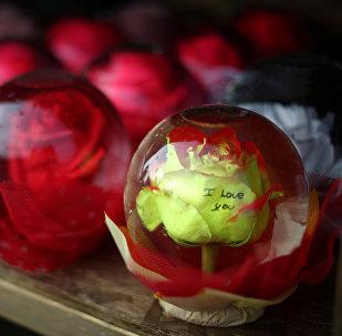 Розы в стеклянных шарах с надписью Я люблю тебя! -  торговля праздничными сувенирами и подарками в День Святого Валентина в Лос-Анжелесе, США