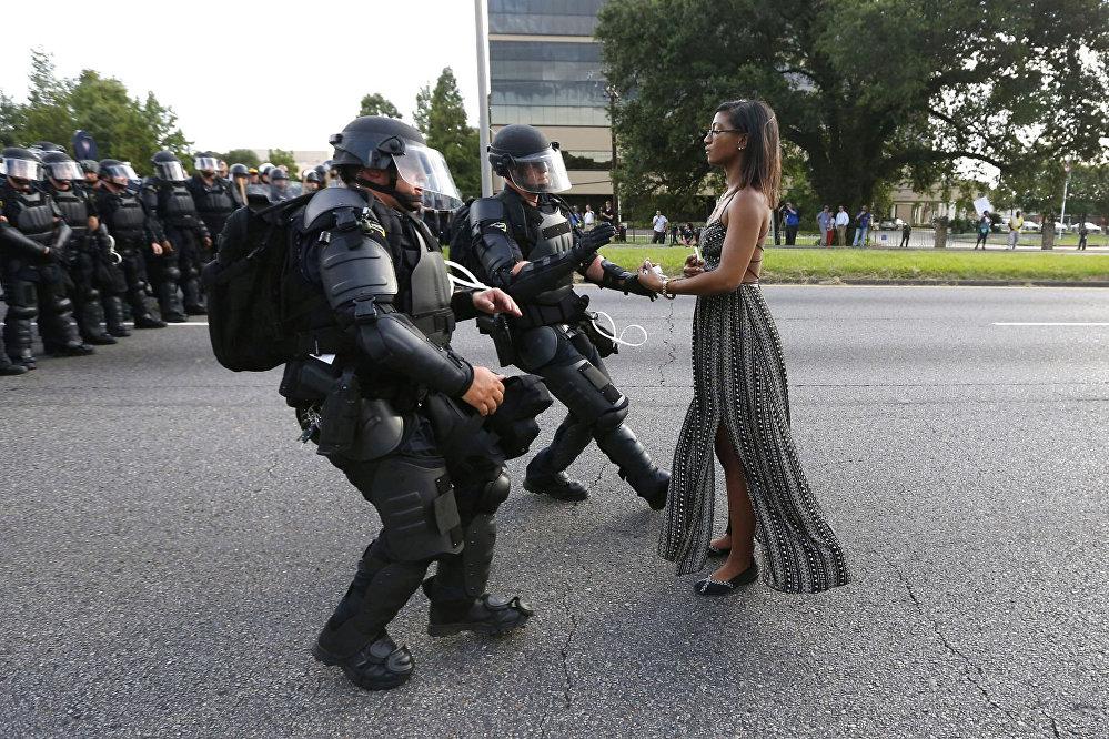 პოლიციის სისასტიკის წინააღმდეგ გამართული საპროტესტო აქციის 28 წლის მონწილე მედდა იეშია ევანსი ხელს უწვდის მის დამკავებენ პოლიციელებს ლუიზიანს შტატში, აშშ. ეს ფოტო ჯონათან ბაჩმანს ეკუთვნის სააგენტოდან REUTERS. ფოტო World Press Photo Awards 2017 კონკურსის ერთ-ერთი პრიზის მფლობელი გახდა