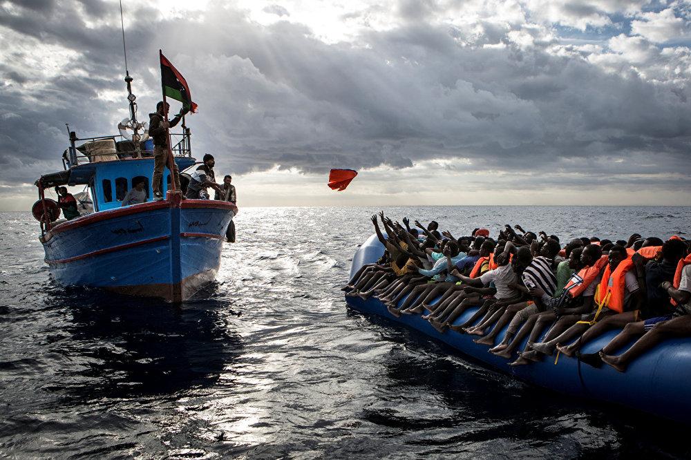 ლიბიელი მეთევზეები სამაშველო ჟილეტებს აძლევენ მიგრანტებს, რომლებიც მათი საზღვარზე გადასვლის ორგანიზატორმა კონტრაბანდისტებმა ღია ზღვაში რეზინის ნავით გაუშვეს იტალიის მიმართულებით. ეს ფოტო მეთიუ უილკოკს ეკუთვნის MOAS.eu-დან, რომელიც არის სერიიდან მიგრაცია ხმელთაშუა ზღვაში. სურათმა World Press Photo Awards 2017 კონკურსზე მესამე პრიზი მოიპოვა კატეგორიაში საგანგებო ახალი ამბავი