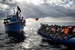 """Ливийские рыбаки бросают спасательные жилеты мигрантам, которых контрабандисты, организовавшие переправу, направили в открытое море на резиновой лодке к берегам Италии. Это фото Мэтью Уилкока из MOAS.eu, сделанное в серии """"Средиземноморская миграция"""", завоевало третью премию World Press Photo Awards 2017 в категории """"Экстренные новости"""""""