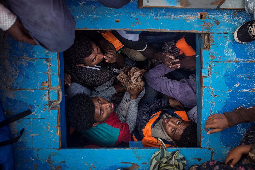 დევნილები აღმოსავლეთ აფრიკის პატარა სახელმწიფო ერიტრეადან ხის ნავის ციხეში სხედან და ცდილობენ ხმელთაშუა ზღვის გადაკვეთით მიაღწიონ ევროპის ნაპირებს. ამ ნავით გადაყავდათ 540 მამაკაცი, ქალი და ბავშვი. ეს სურათი გადაიღო მეთიუ უილკოკმა MOAS.eu-სათვის, რომელიც ხმელთაშუა ზღვის მიგრაციის სერიიდანაა წარმოდგენილი. ფოტომ World Press Photo Awards 2017 კონკურსში მესამე პრიზი მოიპოვა კატეგორიაში საგანგებო ახალი ამბავი