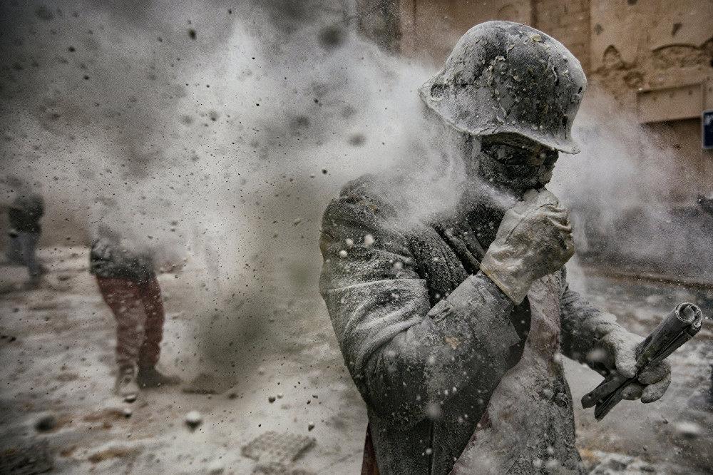 ესპანეთის ქალაქ იბიში უკვე 200 წელია ყოველწლიურად დეკემბერში ტარდება ფესტივალი ფქვილის ომი. ორი მოწინააღმდეგე ჯგუფის წევრები ერთმანეთს ფქვილს აყრიან, ესვრიან კვერცხებს და ფერად მბოლავ შაშხანებს. ეს ფოტო ანტონიო ჰიბოტამ გადაიღო სააგენტოდან Agenzia Controluce. სურათმა World Press Photo Awards 2017 კონკურსში მეორე პრიზი მოიგო კატეგორიაში ხალხი