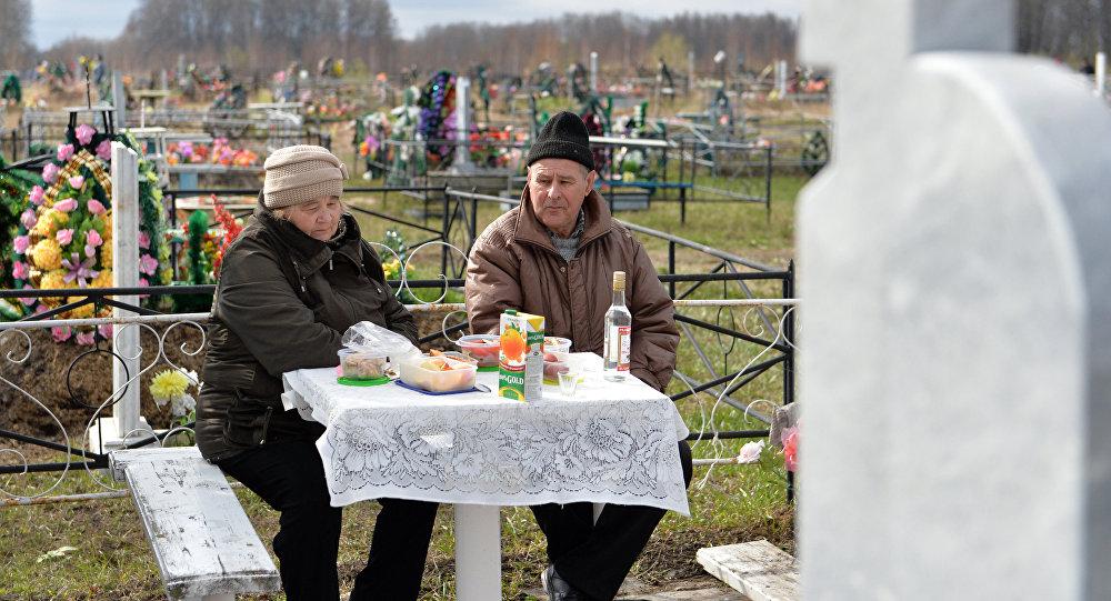 Родственники поминают усопших на кладбище