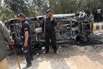 Полицейские на месте, где разъяренная толпа подожгла полицейский фургон в знак протеста после взрыва у могилы суфийского святого Сайед Усман Марванди в южной провинции Синд Пакистана