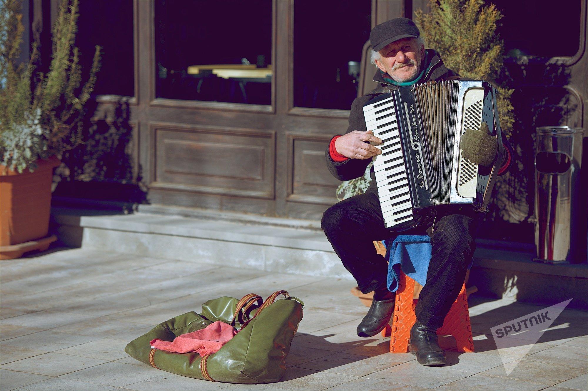 Пожилой уличный музыкант с аккордеоном на одной из тбилисских улиц