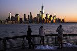 Люди в Хобокен, Нью-Джерси, смотрят на Манхэттен в Нью-Йорке во время заката