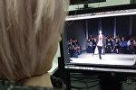 Девушка рассматривает фотографии с показа грузинского бренда Situationist на Неделе мод в Милане