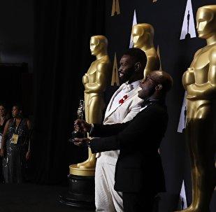 Сценаристы Барри Дженкинс и Тарелл МакКрейни на 89-й церемонии награждения кинопремией Оскар держат в руках свою награду