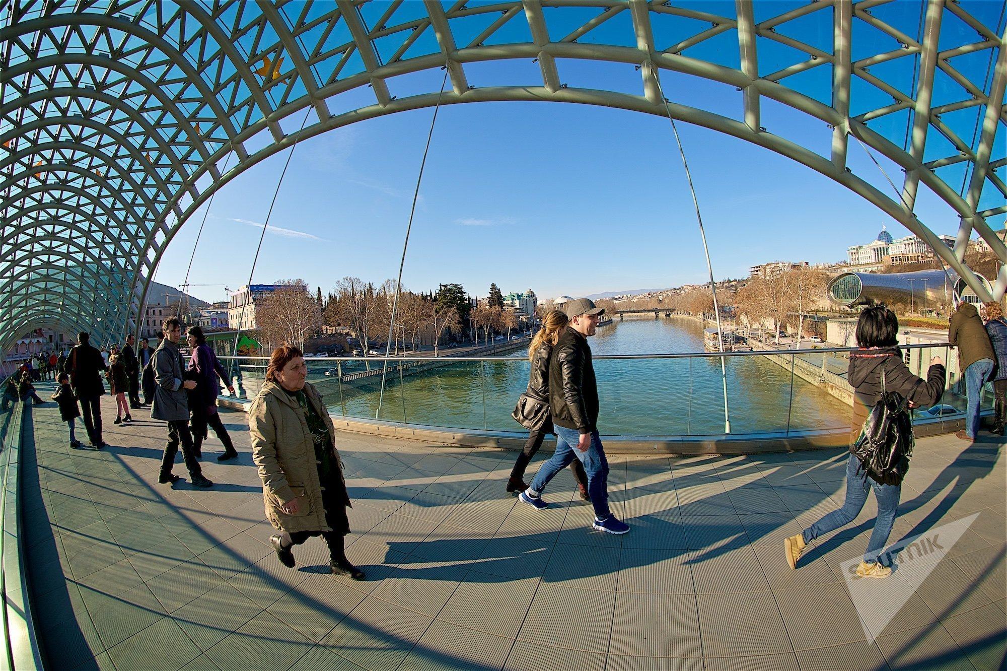 Прохожие на мосту Мира в центре Тбилиси