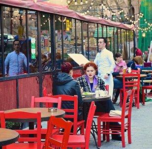 Люди за столиками в одном из тбилисских кафе в историческом центре грузинской столицы
