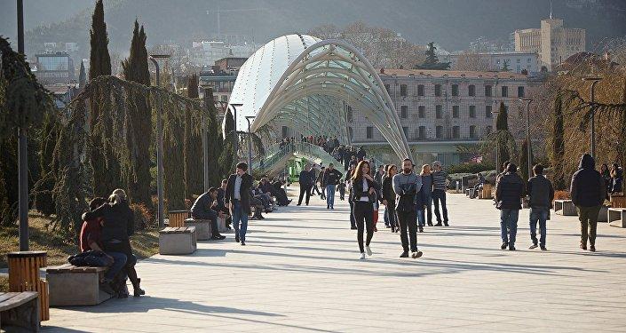 Жители и гости грузинской столицы гуляют в парке Мира на центральной набережной Тбилиси