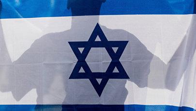 Человек держит в руках флаг Израиля