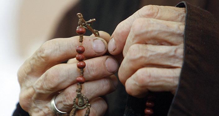 Пожилая женщина молится
