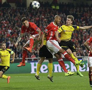 Игроки Бенфика Луизао и Виктор Линделоф прыгают за мячом рядом с Лукашем Пищекем из Дортмунда во время футбольного матча между Бенфика и Боруссия Дортмунд на стадионе Луз в Лиссабоне