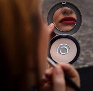 Женщина красит губы помадой