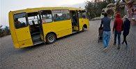 Люди идут к автобусу на стоянке общественного транспорта у парка Мтацминда