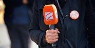Журналист телекомпании Рустави 2 держит в руках микрофон
