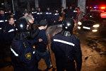 Сотрудники полиции ведут одного из задержанных участников беспорядков в Батуми