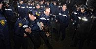 Сотрудники полиции задерживают одного из участников уличных беспорядков в курортном городе Батуми