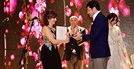 Каха Каладзе награждает женщину-эмигранта