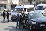 Полицейские стоят возле машин в южном французском городе Грассе после стрельбы в средней школе Токвиля, в результате которой два человека получили ранения