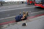 Женщина помогает раненому в результате стрельбы у Вестминстерского моста в Лондоне
