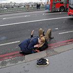 ქალი ეხმარება ლონდონში უესტმინსტერის ხიდთან მომხდარი სროლის შედეგად დაშავებულს