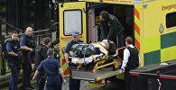 Сотрудники чрезвычайных служб увозят с места стрельбы у Вестминстерского моста в Лондоне раненых и пострадавших